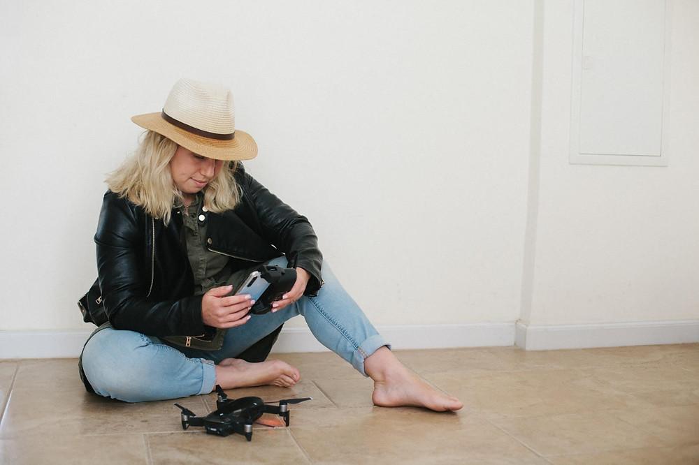Oleh Raquella Raiz sitting on the floor playing with a drone