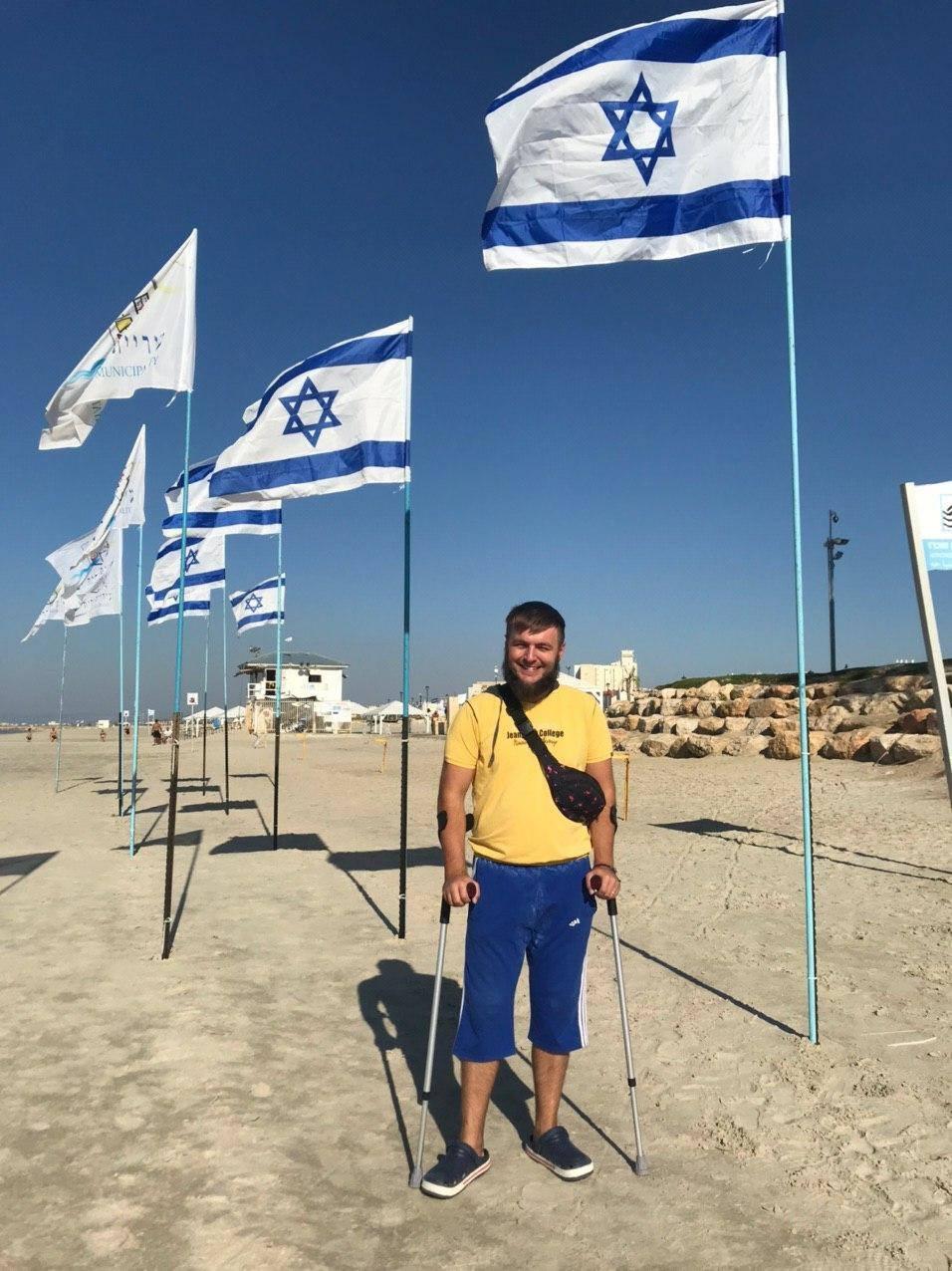 Oleh Andrew Pylypenko standing near a few Israeli flags