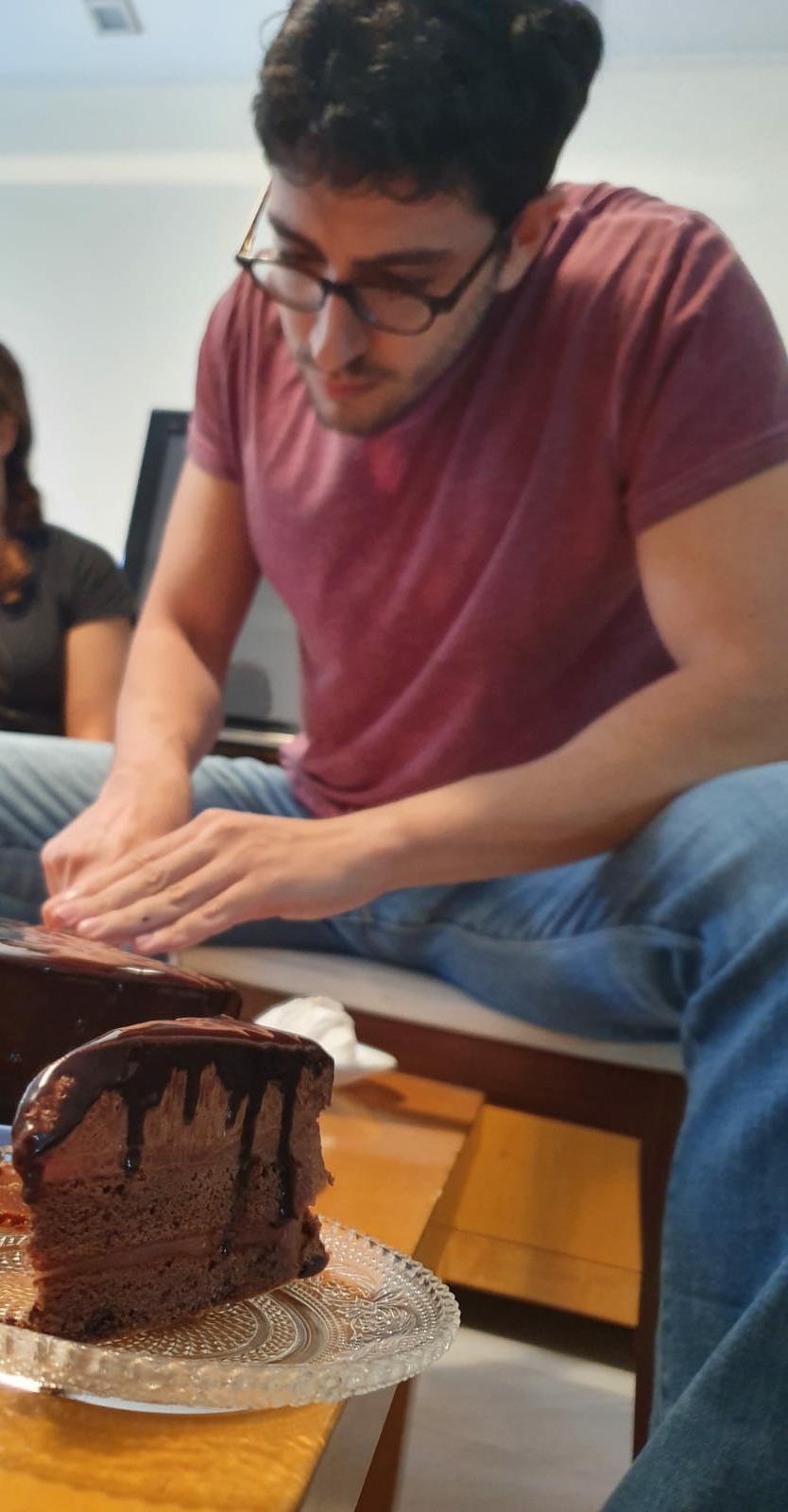 Oleh Hugo Benigeri cutting a chocolate cake