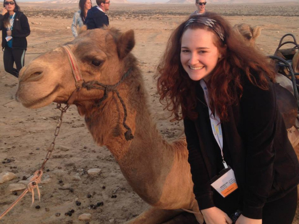 Oleh Rebecca Fox next to a sitting camel