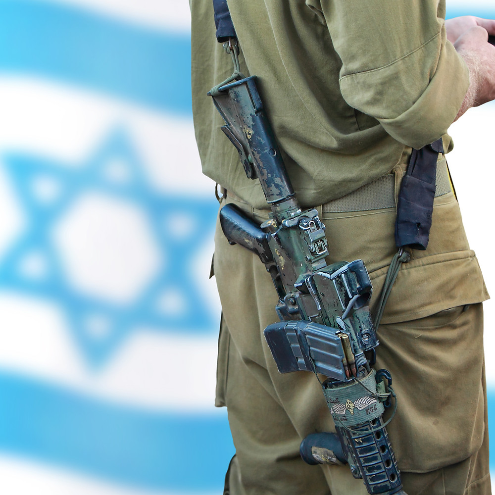 An IDF soldier with a gun standing in remembrance in front of an Israeli flag.