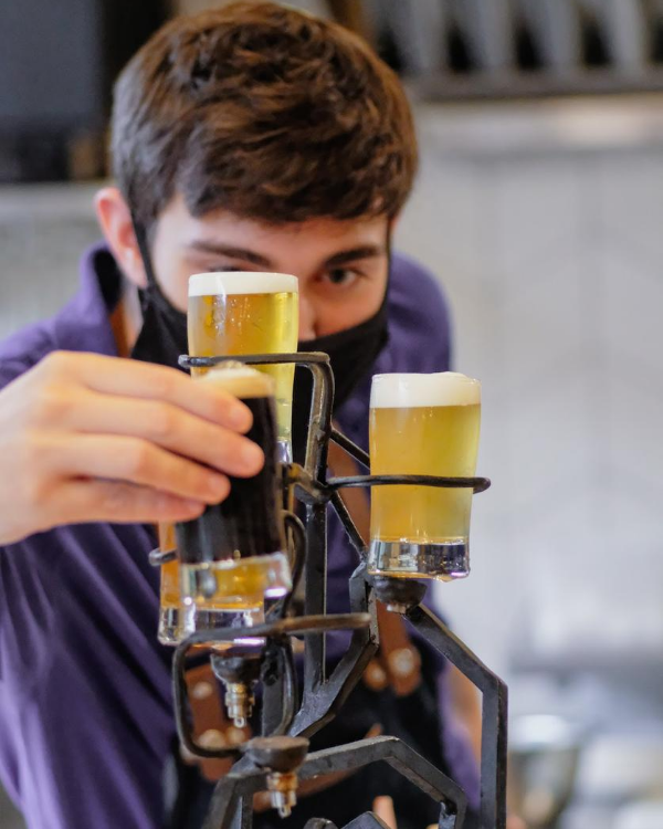 A Hatch Brewery worker setting up beer tasters