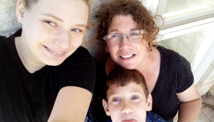 Olah Lauren Adilev with one of her children on her lap and the other taking a selfie of them all
