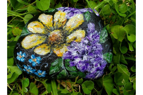 A rock painted with flowers by Kaila Maltz