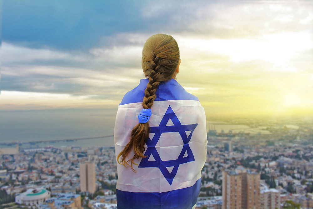 Young woman wearing an Israeli flag over her shoulders looking at a city skyline