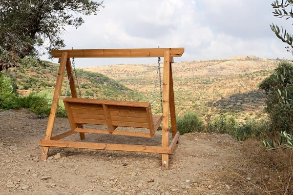A wooden swing at Einot Aner at the edge of the hill overlooking distant hills