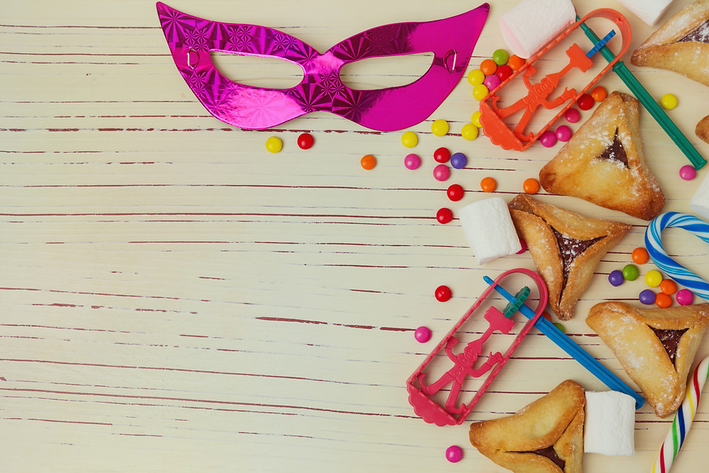 Table top covered in noisemakers, hamantaschen, candy, and a pink mask