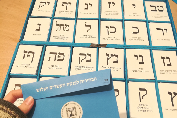 A hand holding an envelope over a box of notes of all the parties running in the Israeli elections