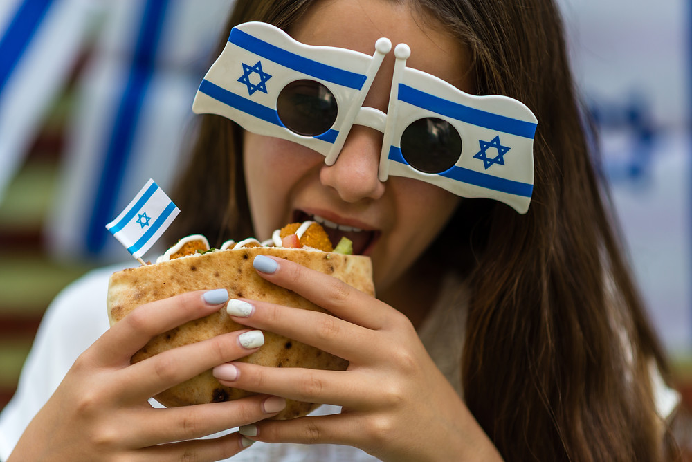 A young girl eating a falafel wearing glasses with Israeli flags to celebrate Israel