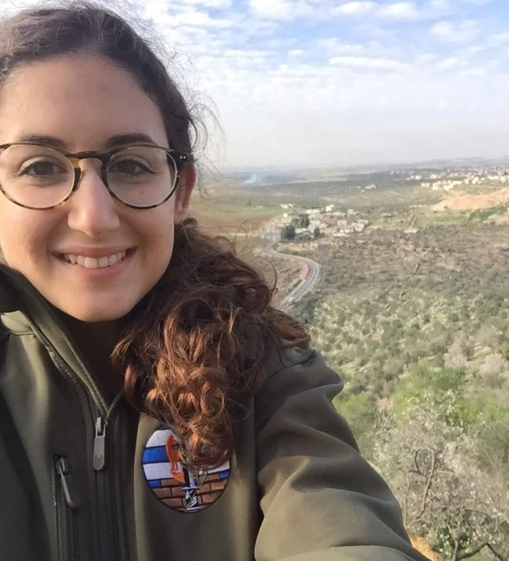A selfie of Olah Chantelle Leiderman in her IDF uniform with hills behind her