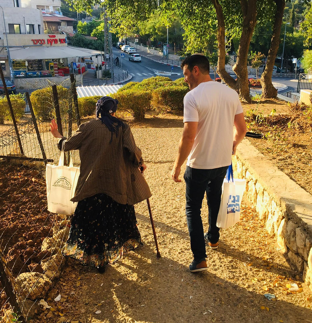 A young man accompanies an older woman to vote in the Israeli elections