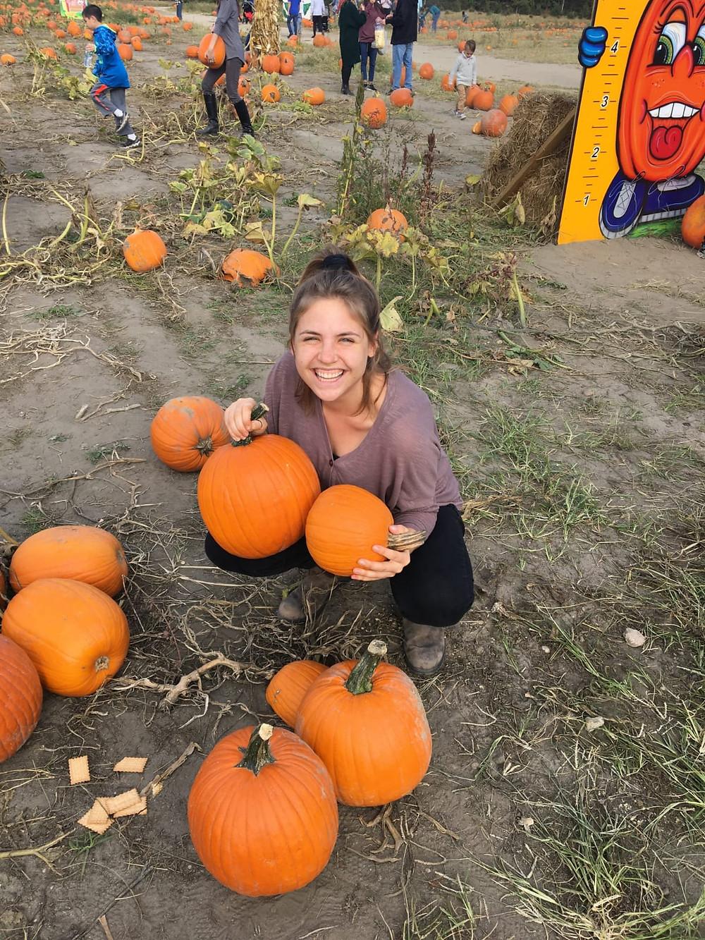 Oleh Kayla Rosen picking pumpkins in a pumpkin patch