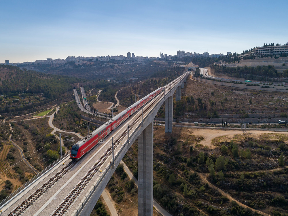 Aerial view of a red train on a bridge over Highway 1 with Jerusalem in the background