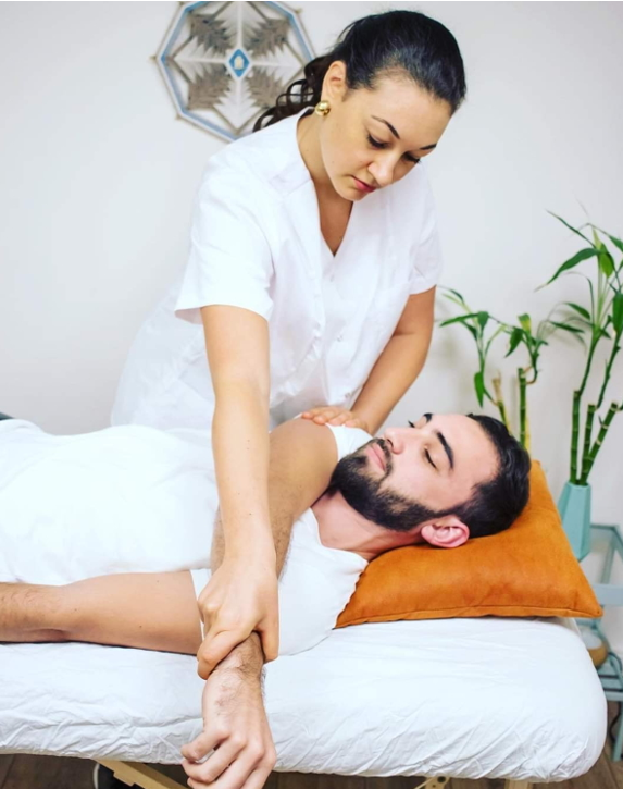 Olah Yudith Guttman giving stretching the arm of a male client