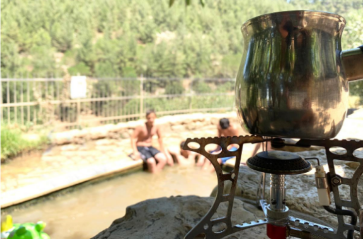 Close up of a #Pakal_Kafe kit with 4 youth in the Ein Sadjma pool in the background