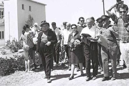Prime Minister Levy Eshkol and his wife among a crowd of people walking through Kibbuts Eilot