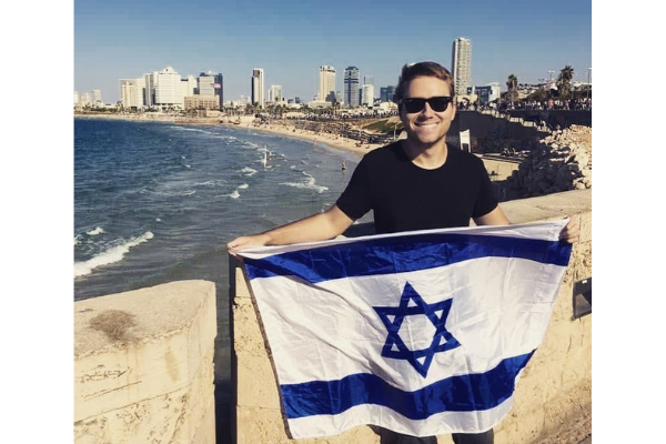 A young man holding an Israeli flag on a promenade overlooking Tel Aviv and the Mediterranean Sea