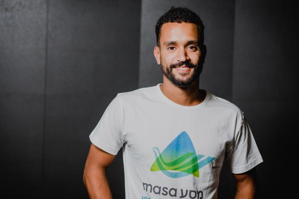 A smiling male wearing a Masa program t-shirt