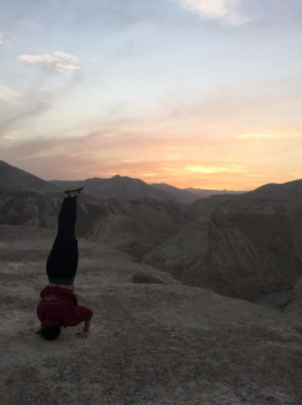 #Meet_the_Oleh, Maddie De Silva, doing a head stand on top of a mountain in the desert at sunrise