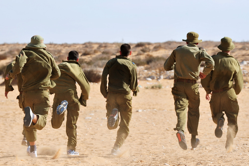 5 IDF soldiers wearing green uniforms running on sand