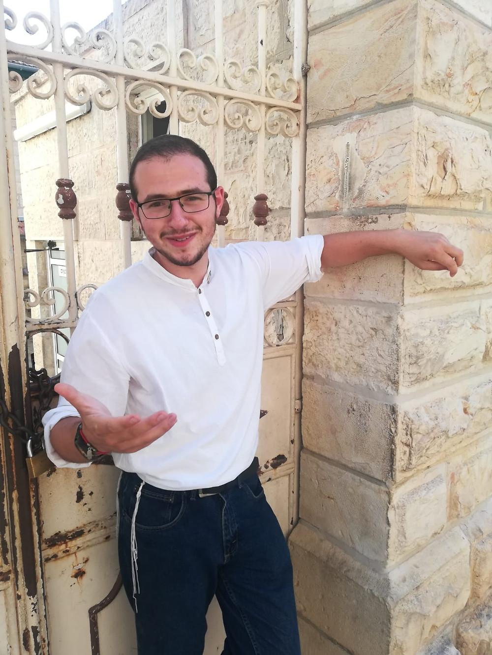 Oleh Judah Powers standing before a house gate