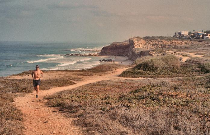 Oleh Frederic Simon running on a dirt path along the sea