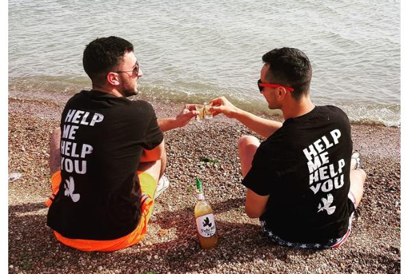 Hilal and Yanai sitting on the beach clinking shotglasses of Tubi 60