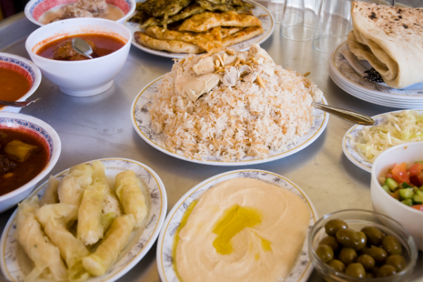A table covered in various dishes pilled with food