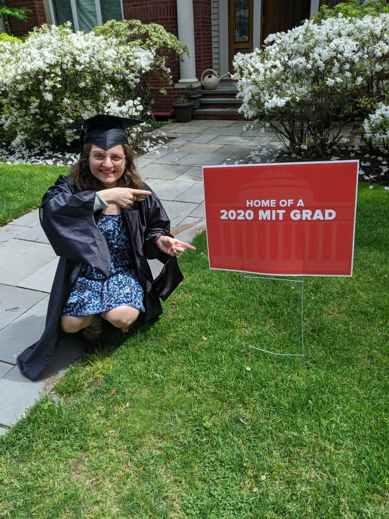 Amy Vogel wearing a graduation gown and cap while pointing to a sign that reads 'home of a 2020 MIT Grad'