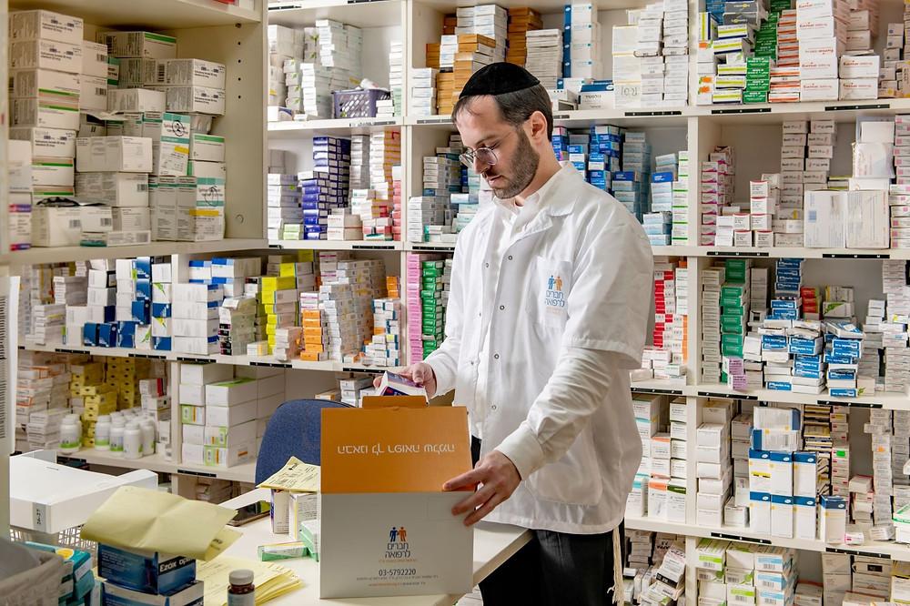 A Haverim L'Refuah pharmacist packing a box of medicine