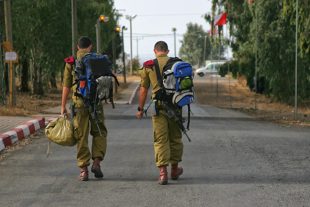 Two IDF soldiers walking down a road with large backpacks