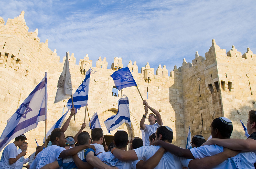 Israeli youth wearing white and holding Israeli flags dancing outside the Old City on Jerusalem Day (Yom Yerushalayim)
