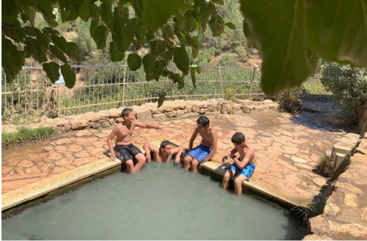 4 boys sitting on the ledge of Ein Sadjma pool