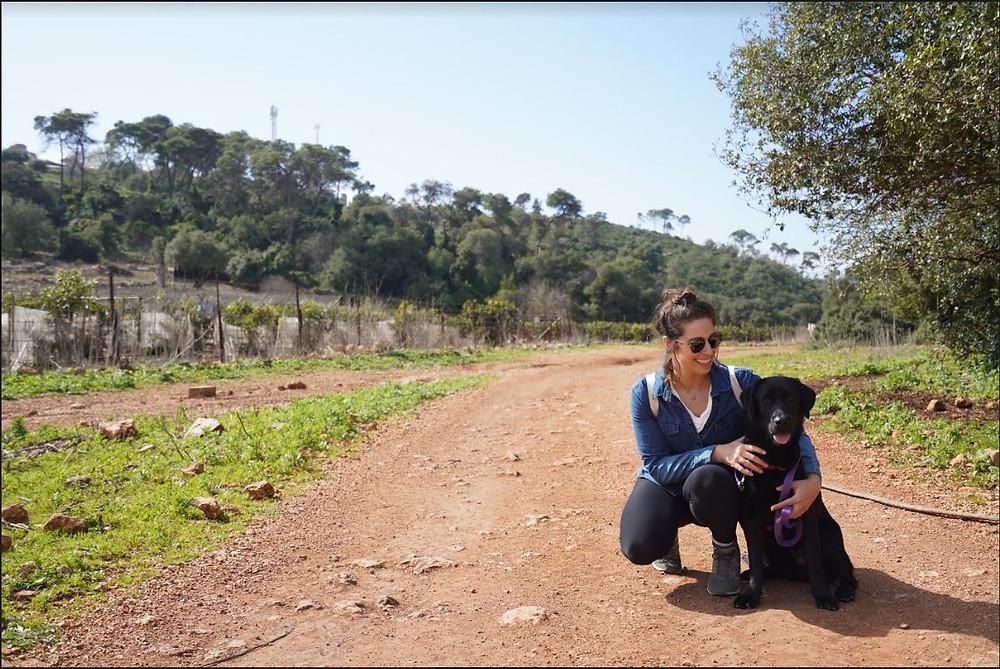 Olah Rachel Belsky on a path petting her dog
