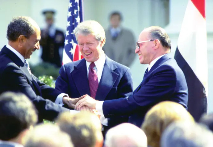 Prime Minister Menahem Begin, President Carter, and President Anwar Sadat shaking hands in Washington, D.C