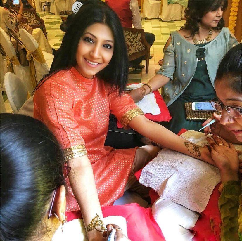 Eddna Samuel receiving henna on both her arms.
