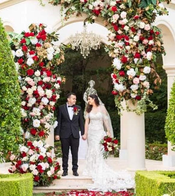 Olah Chantelle Leiderman and her husband holding hands under a wedding huppah