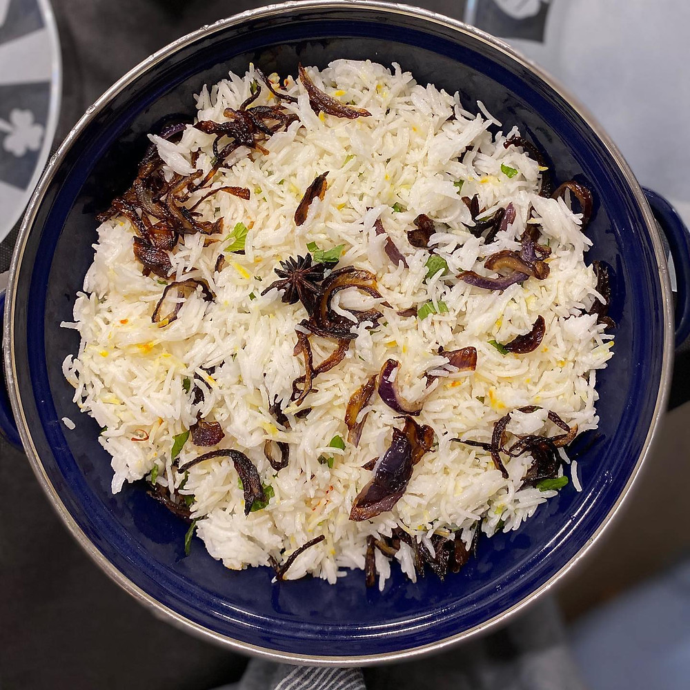 An Indian rice dish in a large blue bowl with various vegetables