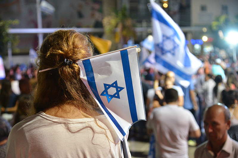 A young woman with a small Israeli flag in her hair facing a crowd of people celebrating with Israeli flags