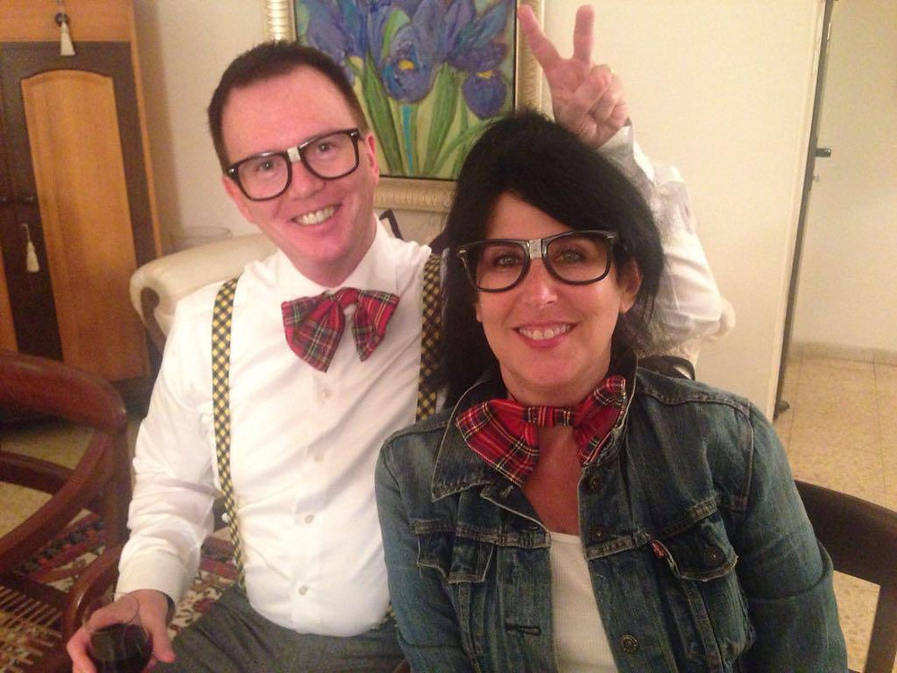 Mark Fitzsimmons giving bunny ears to Eedie Fitzsimmons while both in oversized glasses and plaid bowties