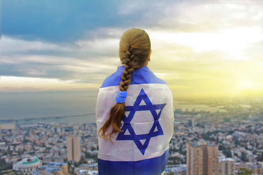 Young girl with a braid wearing an Israeli flag on her back looking over Tel Aviv