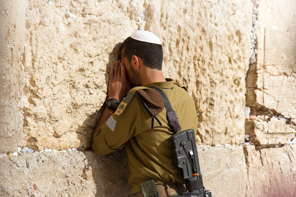 Young Israeli male IDF soldier in a green uniform and gun on his back has his face pressed against the Western Wall