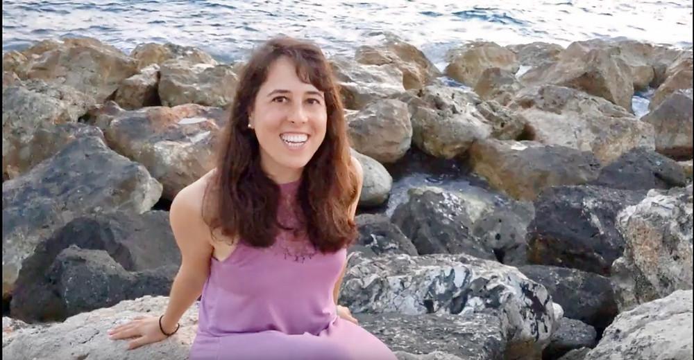 Karen Biala sitting on rocks by the sea
