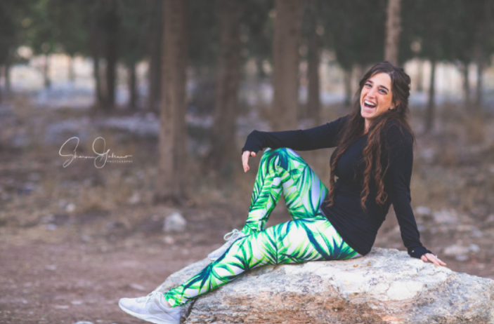 Esther Taub of Esther Taub Fitness sitting on a rock in a forest