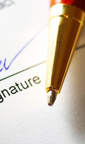 Picture shows a freshly penned signature in the background, with the tip of a ball point pen in the foreground. Symbolizes the sign-up process for a mailbox rental at Travellers Mailbag.