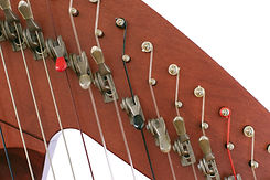 Levers and strings of folk harp close up