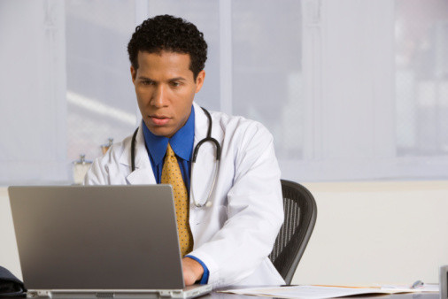Male doctor working on a computer