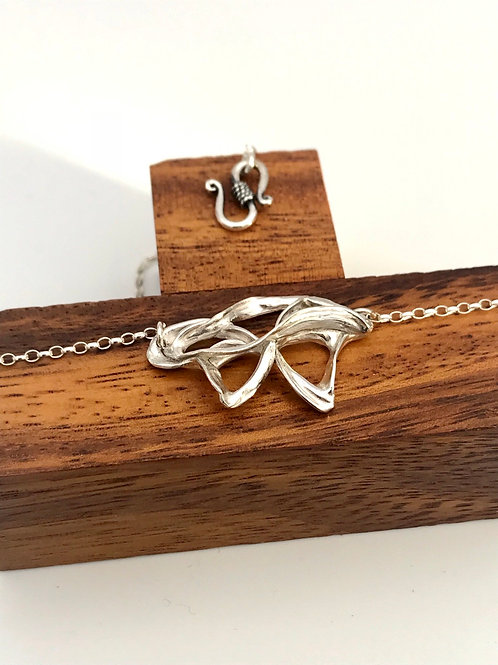 """Swirling Bow"" Silver Pendant."