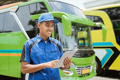 male-bus-crew-member-uniform-hat-smiles-while-using-digital-tablet-against-backdrop-bus-fl