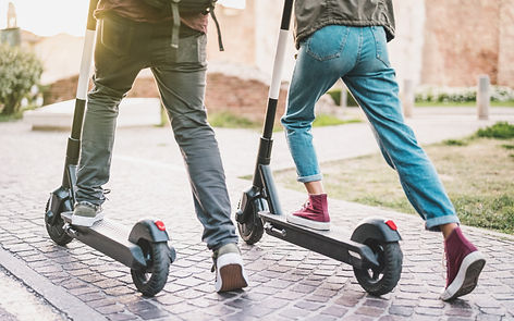 close-up-people-couple-using-electric-scooter-city-park.jpg